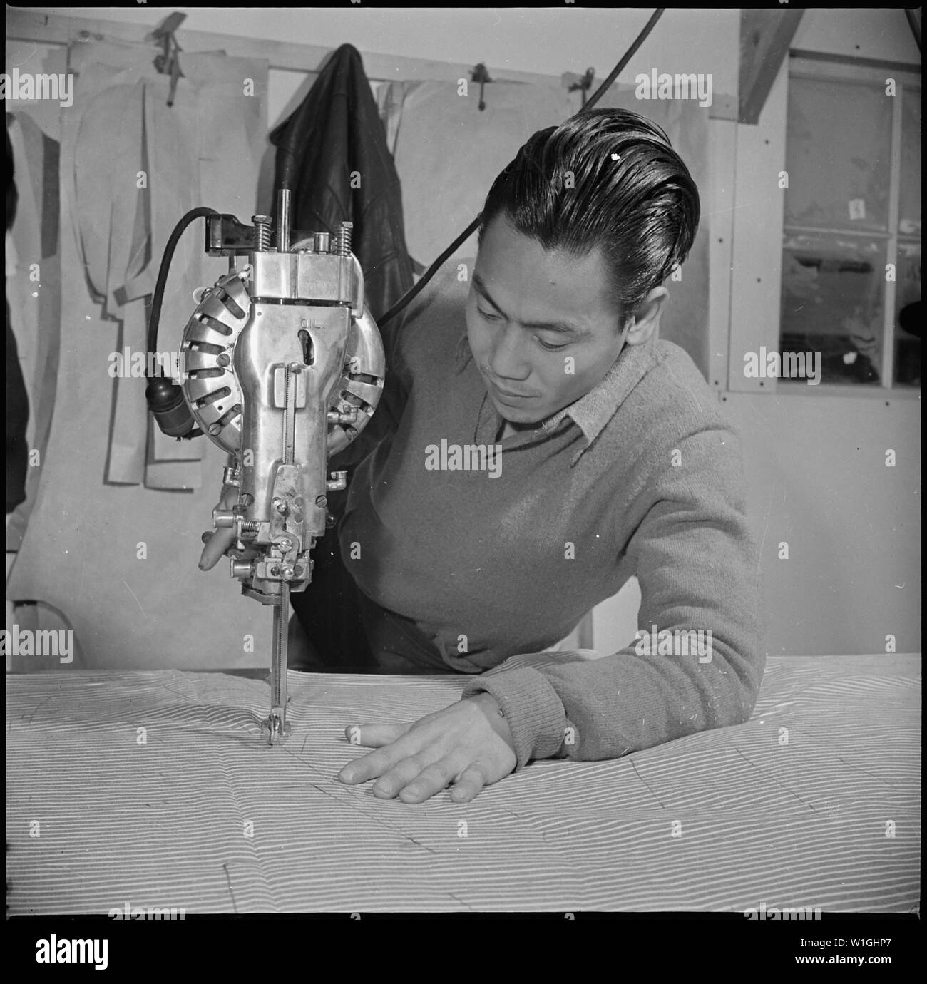 Manzanar Relocation Center, Manzanar, California. Bert Miura, ex fabbrica di indumento lavoratore dal basso . . .; Portata e contenuto: tutta la didascalia per questa fotografia si legge: Manzanar Relocation Center, Manzanar, California. Bert Miura, ex fabbrica di indumento lavoratore di Los Angeles, California, è ora lavora nel reparto taglio nella fabbrica di indumento. Egli è mostrato il taglio di materiale per il materasso di incollamento. Tutti i lavori in questa fabbrica di indumento, che produce abbigliamento da lavoro per lavoratori evacuee, è fatto dal giapponese residenti nordamericani. Immagini Stock