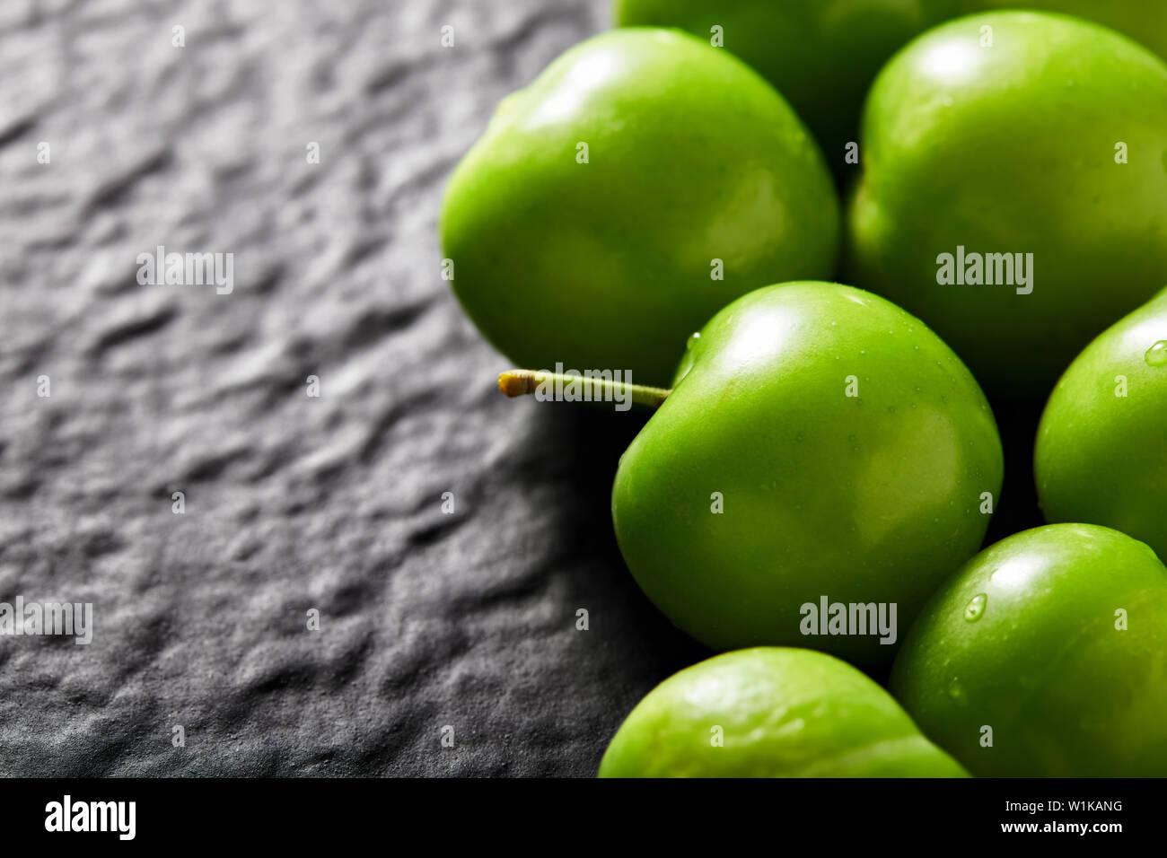 Cumulo di green gage prugna su nero testurizzato di pietra con sfondo spazio copia. Close up vista macro. Immagini Stock