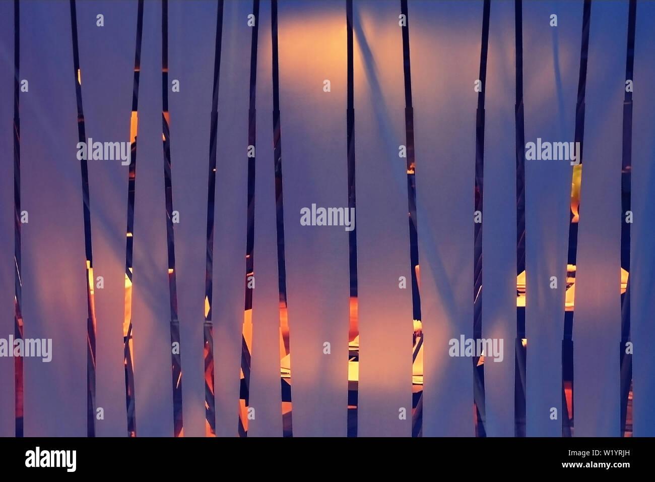 In vetro smerigliato con verticale strisce trasparenti, dietro al quale vi è una sala illuminata, astratta interiore di sfondo giallo e viola i colori. Foto Stock