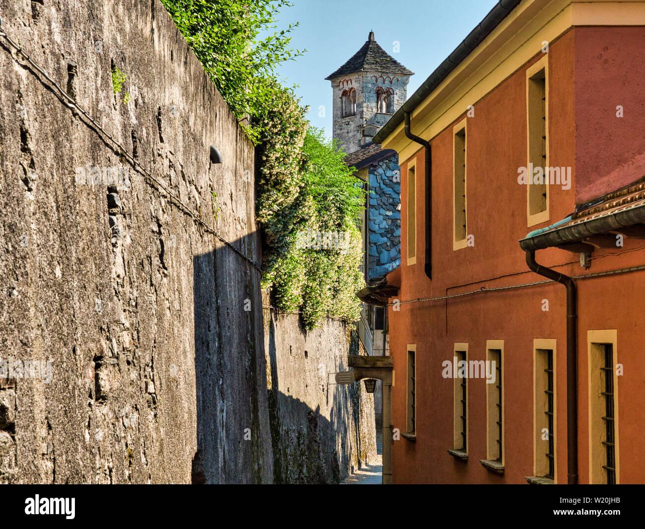 Strada desolata con via e pareti di pietra sull'Isola di San Giulio nel Lago d'Orta con il campanile di San Giulio Basilica in background durante una Foto Stock