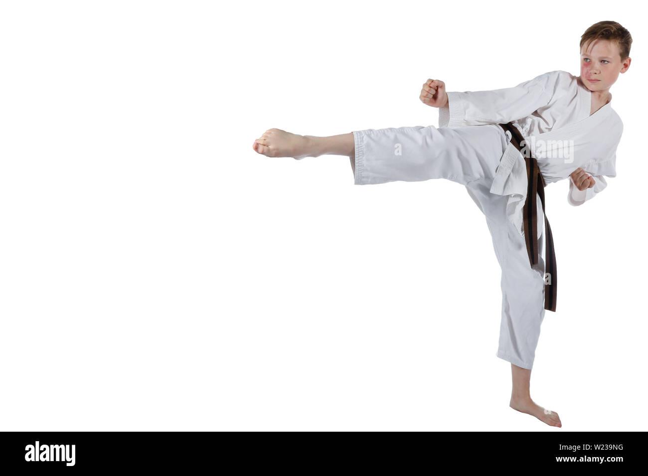 Teenage ragazzo caucasico indossando il karategi facendo un gancio kick Immagini Stock