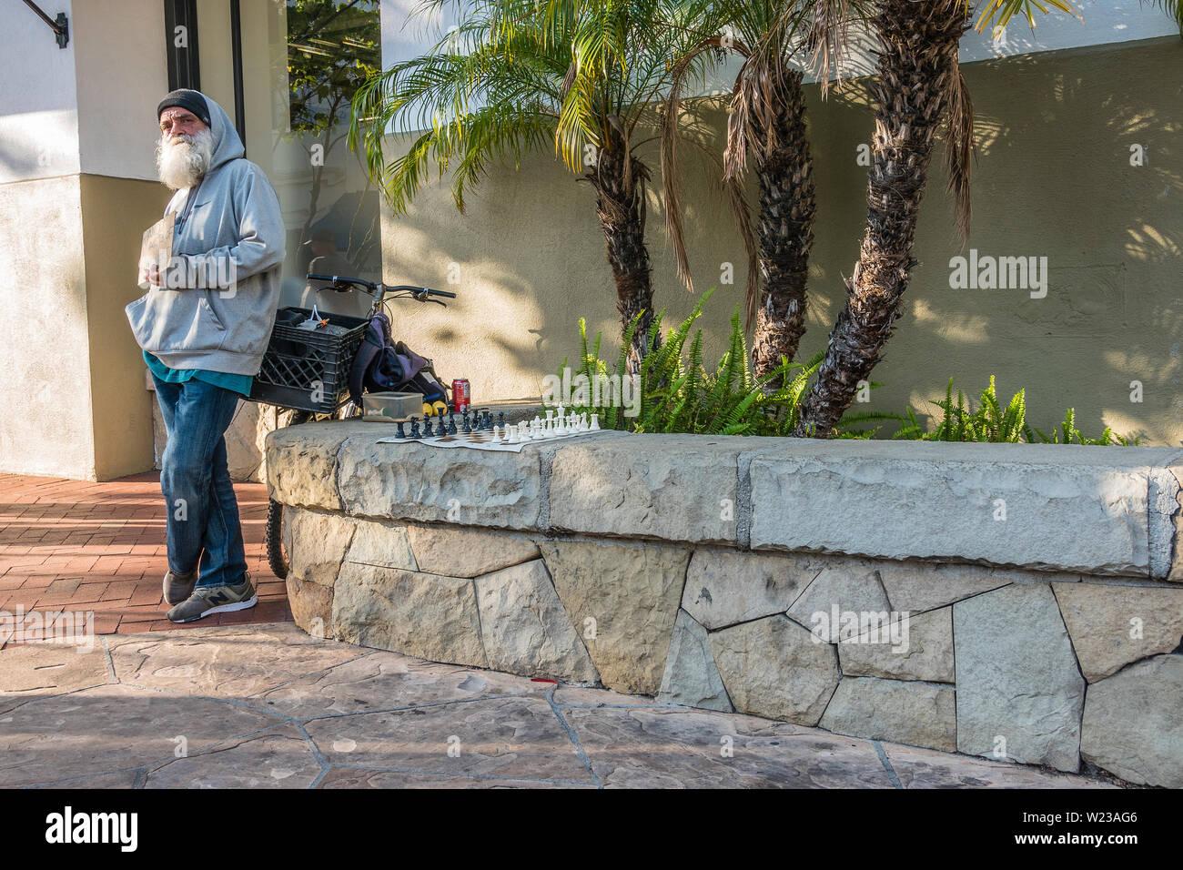 Un vecchio maschio caucasico detiene un segno stimolante passanti per un gioco di scacchi. Egli ha la sua scacchiera impostare pronto per la riproduzione su un basso muro di pietra accanto a Foto Stock