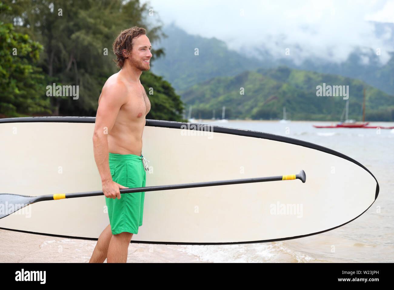 Stand Up Paddle board beach uomo facendo paddleboard andando paddleboarding nelle Hawaii. Giovani caucasici atleta maschio sulla spiaggia hawaiana su Vacanze estive Vacanze viaggi. Immagini Stock