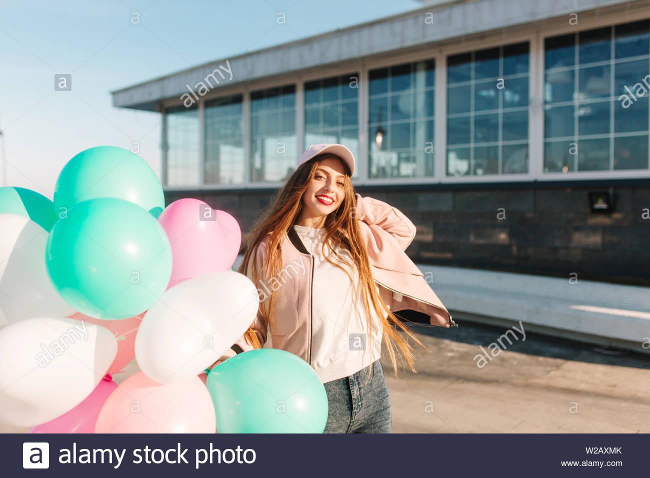 d1892c126c Attraente ragazza bruna con scintillante sorriso lieto di posa holding  palloni di elio dopo la passeggiata