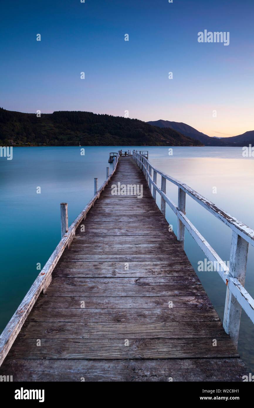 Il pittoresco molo illuminato al crepuscolo, Kenepuru Sound, Marlborough Sounds, Isola del Sud, Nuova Zelanda Foto Stock
