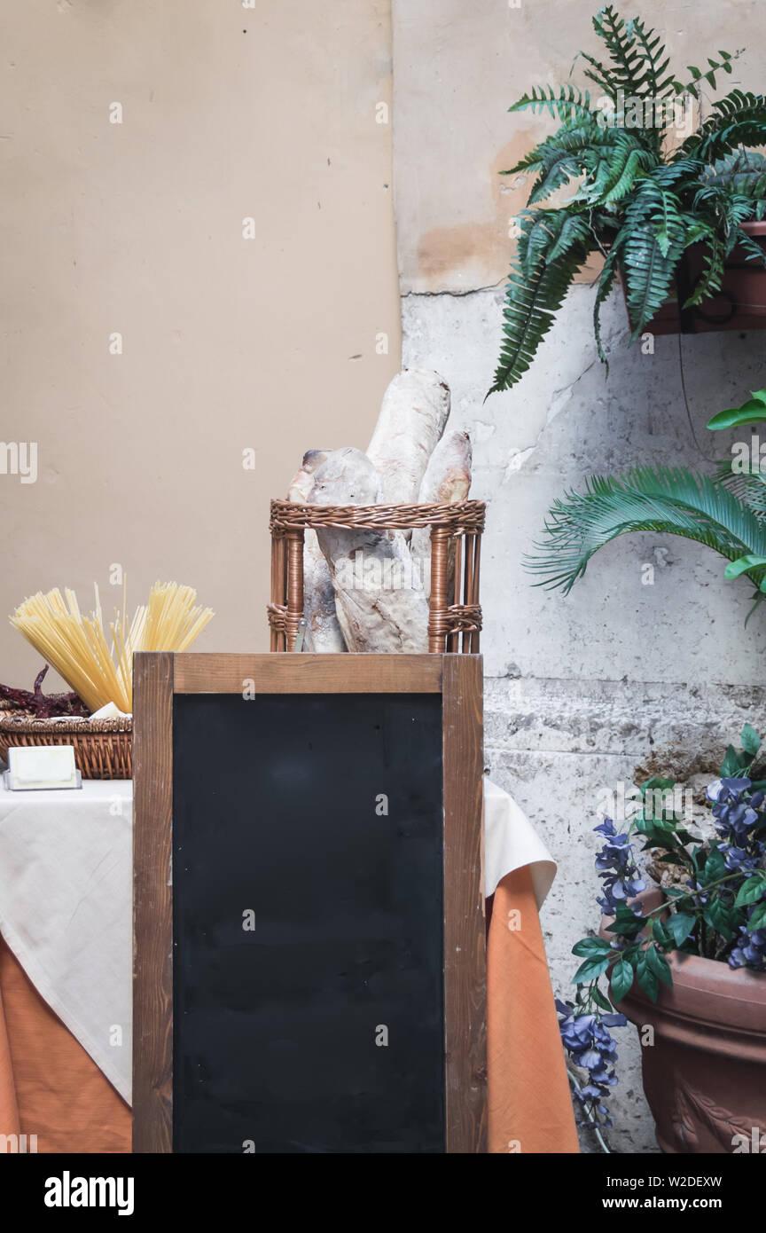Vuoto in stile italiano vera lavagna nella parte anteriore della tavola con pasta e pane, circondato da piante Foto Stock