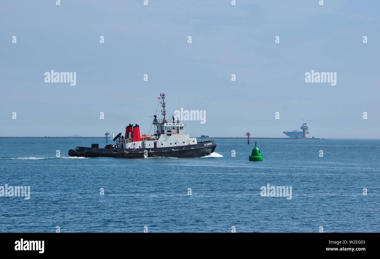Unità gemelle Trattore rimorchiatore, SD attenta, in Plymouth Sound con portaerei HMS Queen Elizabeth oltre il frangiflutti, Devon, Inghilterra, Regno Unito Immagini Stock