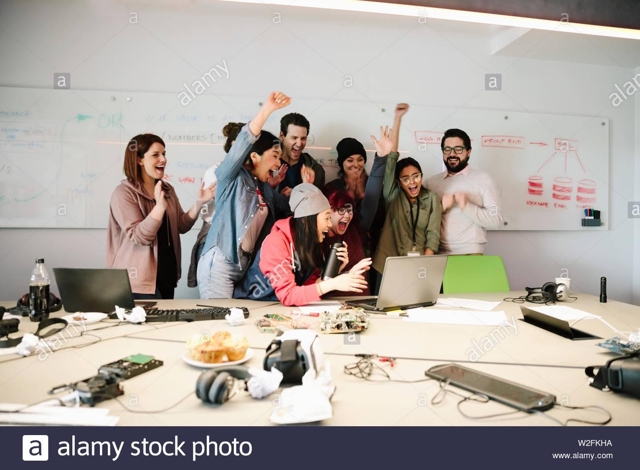 Entusiasti programmatori di computer il tifo al computer portatile in sala conferenza incontro Immagini Stock