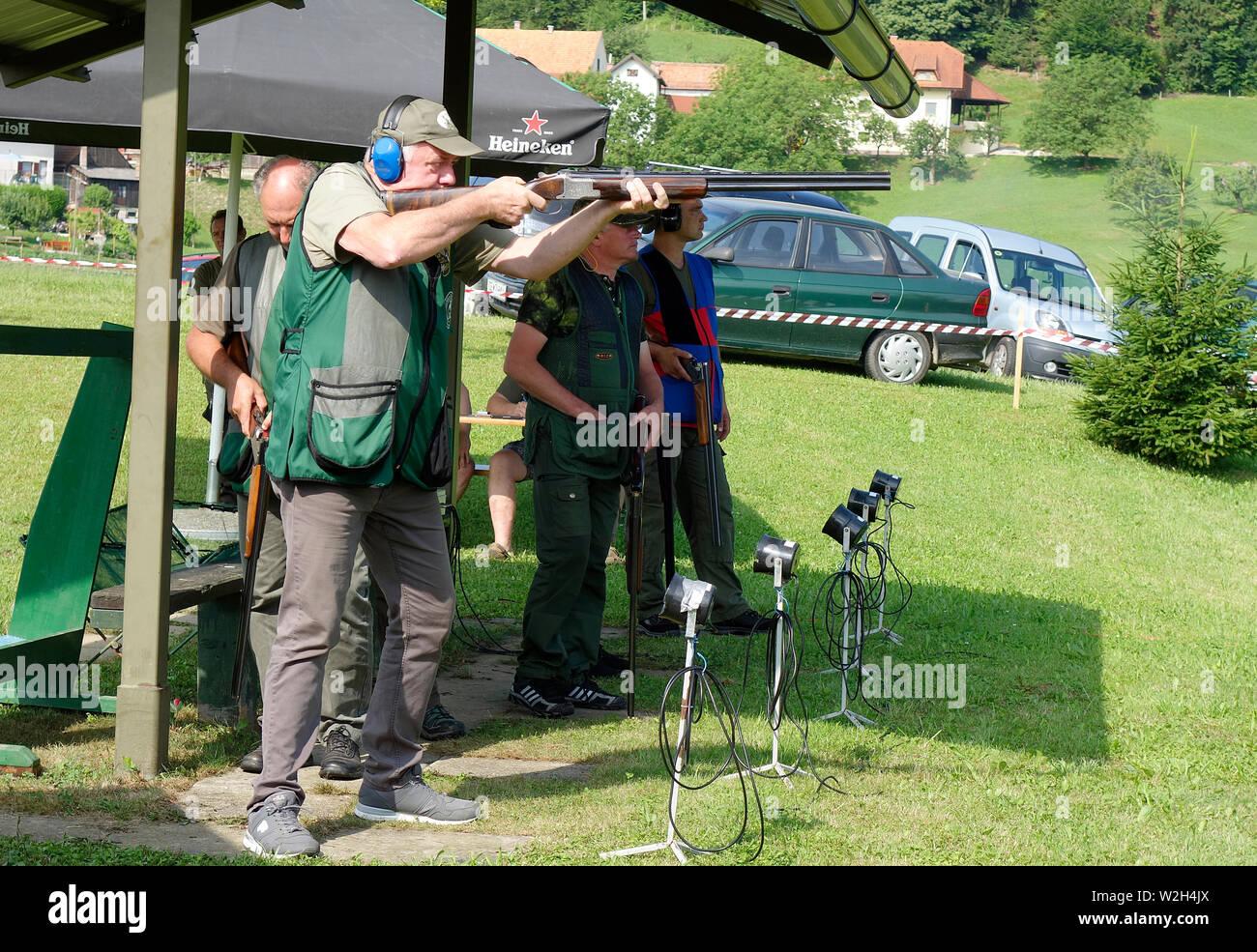 Scalzone angelo. I concorrenti le riprese fucili a canna liscia a bersagli di argilla. Immagini Stock