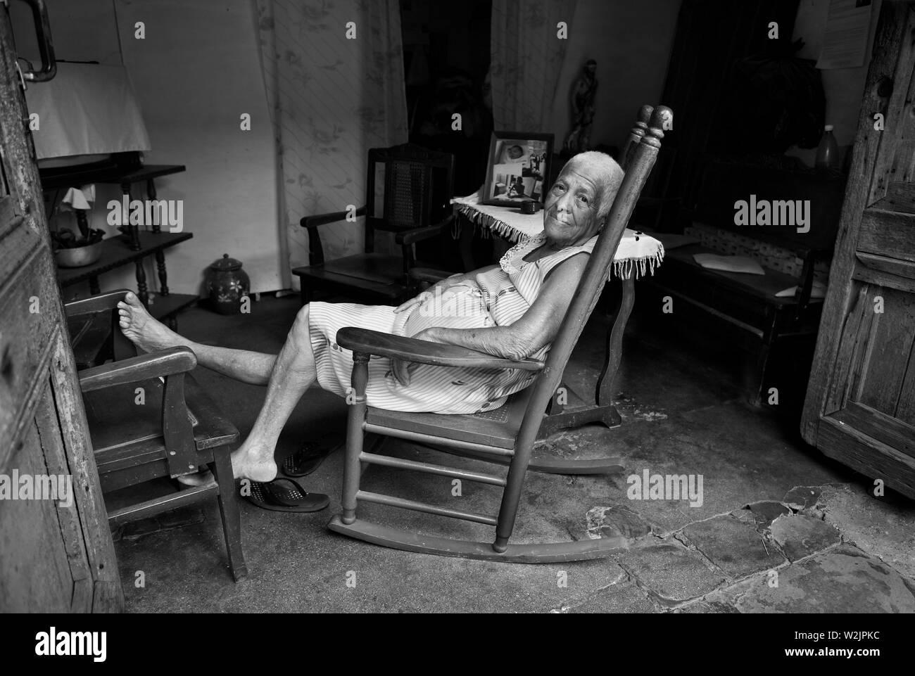 Trinidad Cuba: La Signora riposa nel pomeriggio nella sua sedia a dondolo che guarda su come il mondo la fa pas vicino. Foto Stock