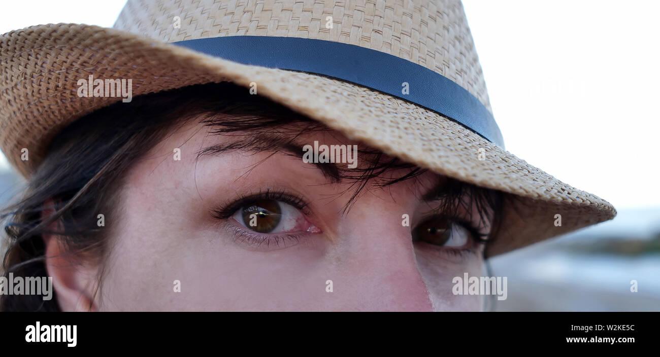 Ritratto di un marrone-eyed brunette in un cappello guardando dritto verso la fotocamera con occhi grandi Foto Stock