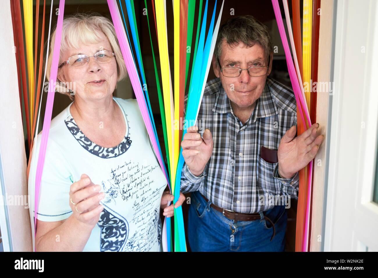 Divertente coppia senior a piedi attraverso colorate strisce tenda a casa Foto Stock