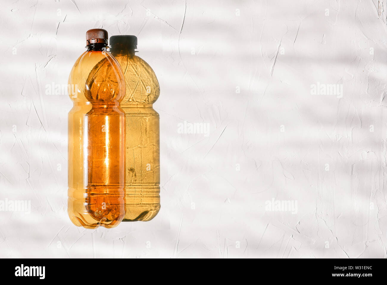 Bottiglia vuota su sfondo bianco. Dal flacone cade hard ombra. Bright sole splende. Concetto di ecologia, inquinamento di terra o la produzione di bottiglie. Copia Immagini Stock