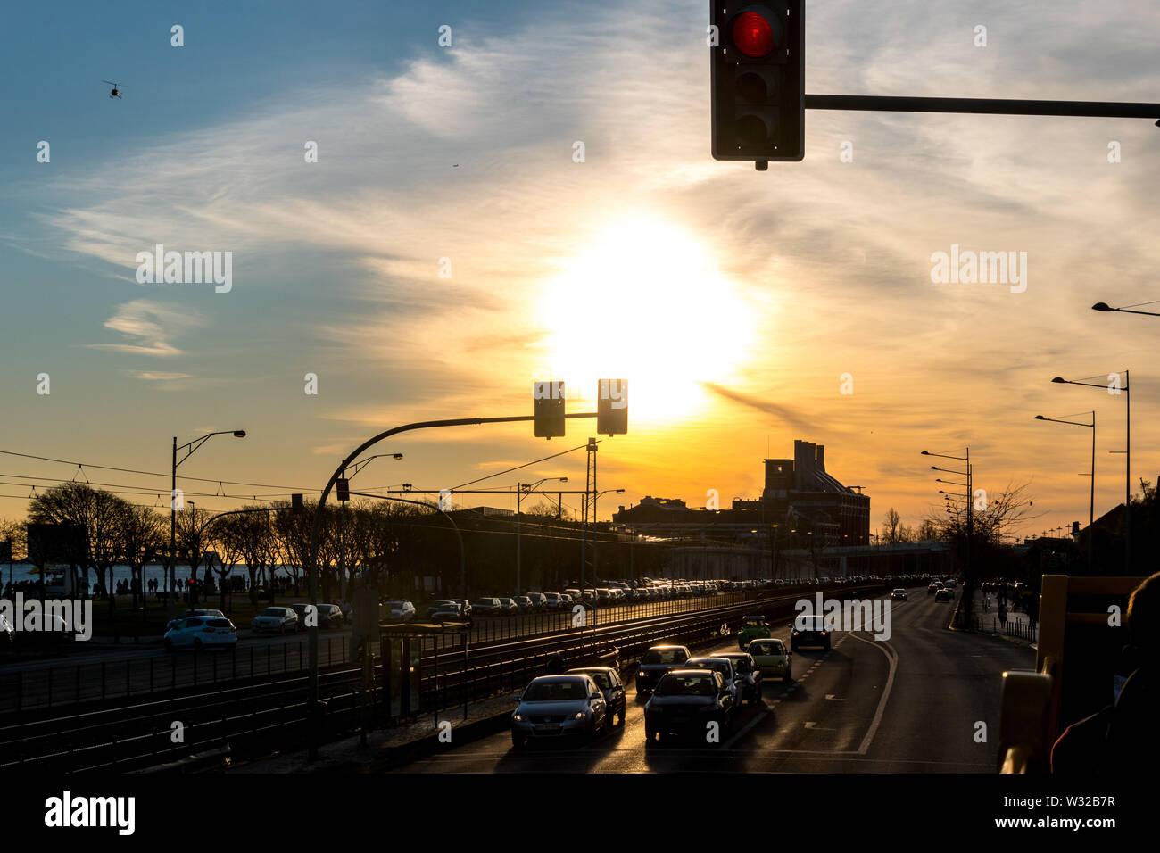 Guardando verso il basso una strada di Lisbona con traffico pesante durante il tramonto. Foto Stock