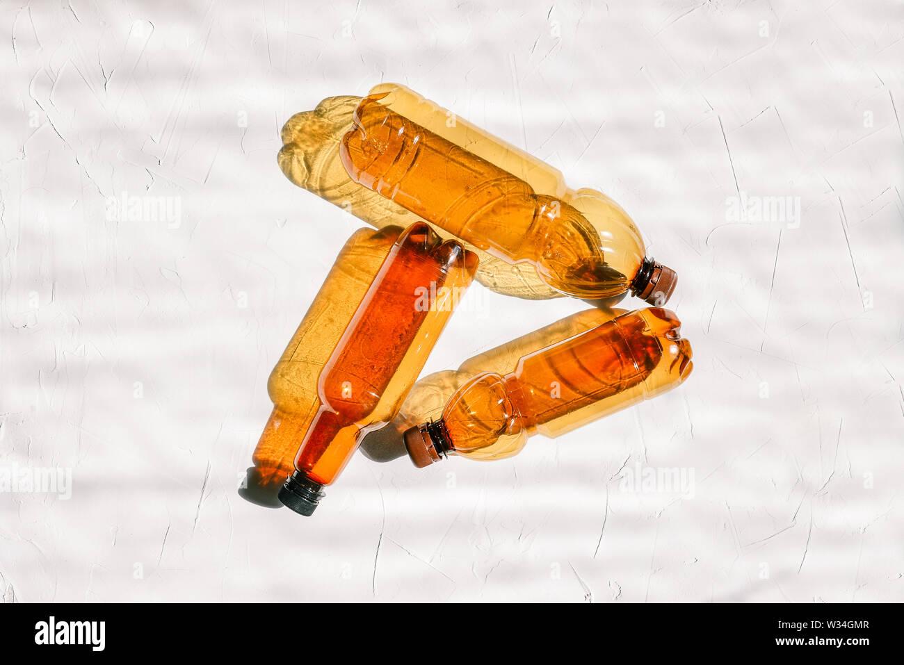 Lo sfondo da le bottiglie di plastica vuote. Tre bottiglie di plastica su uno sfondo bianco. Il concetto di terra inquinamento da rifiuti, riciclaggio e riciclaggio di Immagini Stock