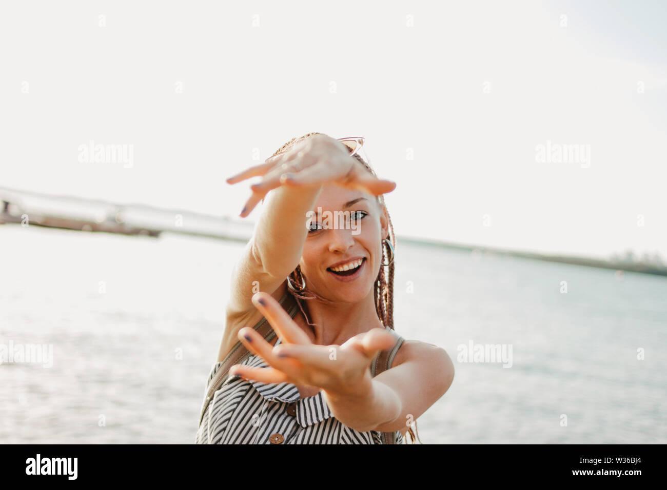 Felice di spensierata giovane donna con trecce africane godere la sua vita sulla spiaggia, estate tempo di vacanza Foto Stock