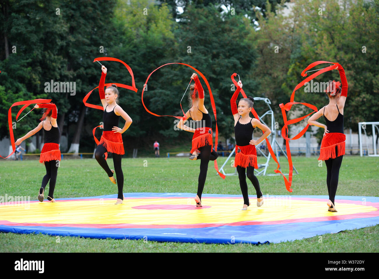 Gruppo di poco la ginnastica artistica le ragazze a fare gli esercizi con nastri su un campo di calcio. Giugno 20, 2019.Kiev, Ucraina Foto Stock