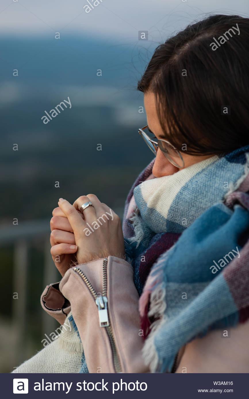 Closeup colpo di una bella donna con sciarpa che mostra il suo anello di fidanzamento sfondo sfocato Immagini Stock