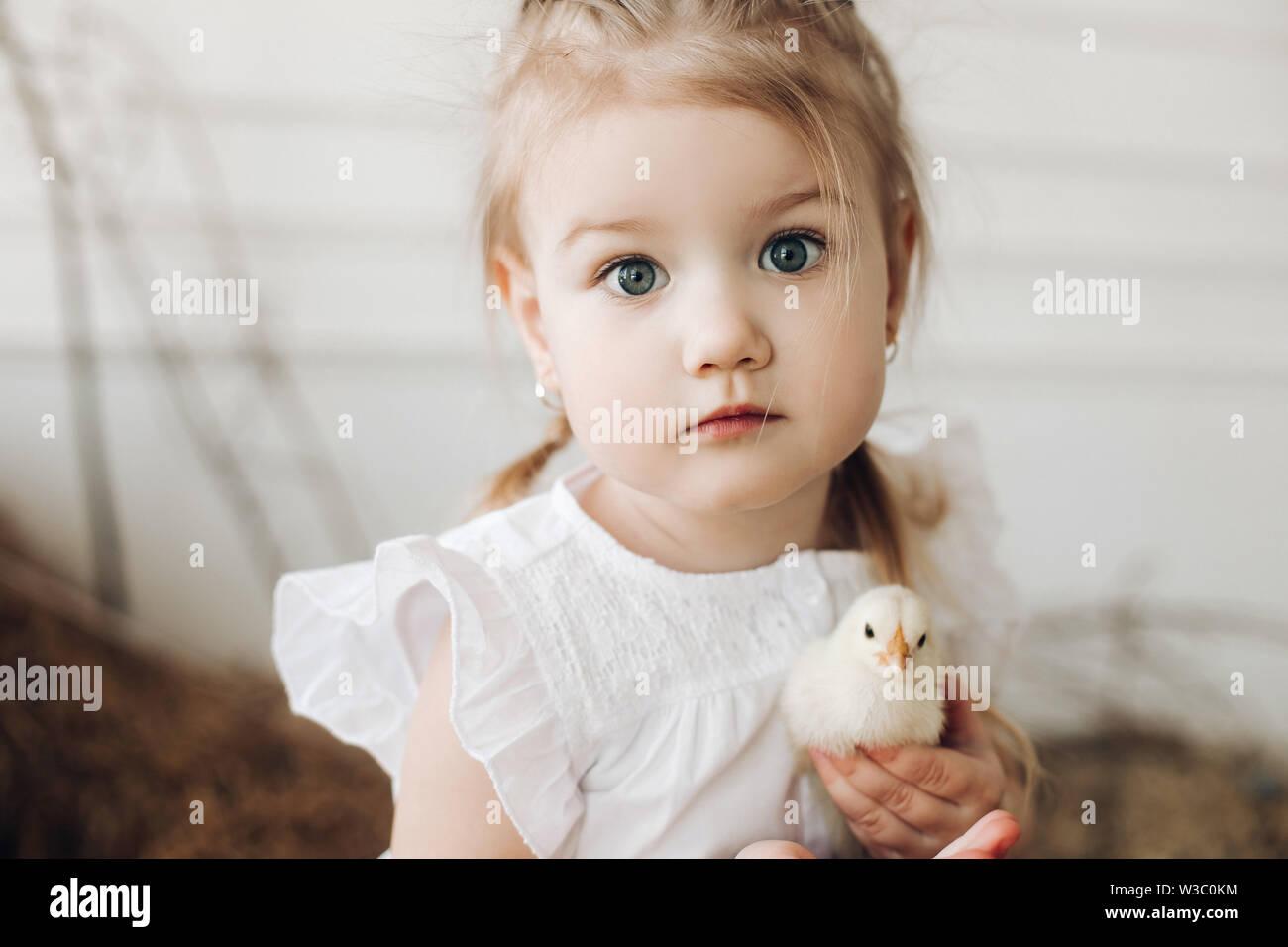 Bella ragazza con grandi occhi più belli mantenendo piccolo pulcino Foto Stock