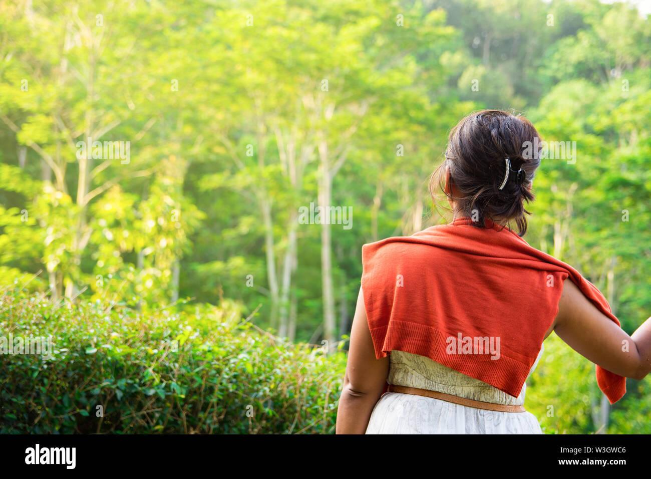Donna che guarda al Forest View nel tardo pomeriggio luce dorata. Uno stile di vita all'aperto Concetto di immagine con modello sconosciuto. Foto Stock