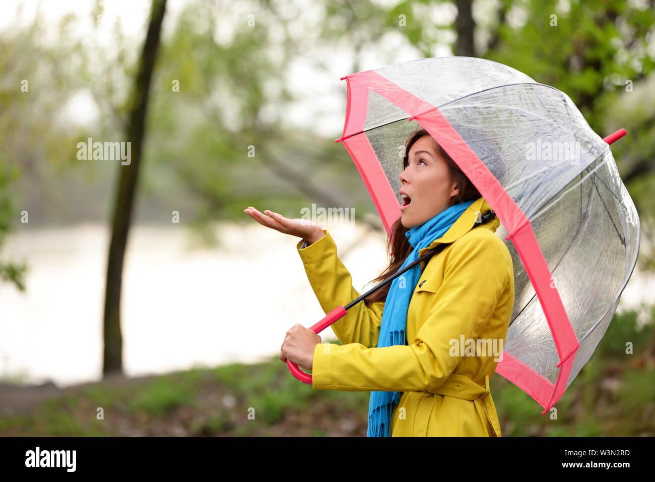 La donna a piedi sotto la pioggia in autunno foresta. Bella ragazza si sente le gocce di pioggia a piedi nella foresta dal lago in autunno. Razza mista Asian Caucasian modello femminile con divertenti ecxpression. Foto Stock