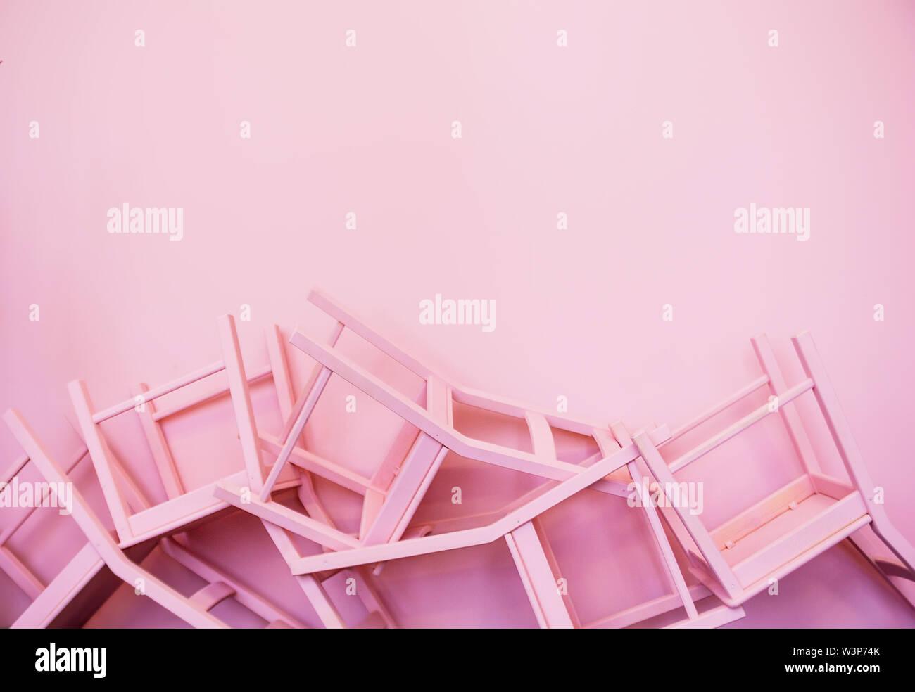 Molte sedie rosa capovolto contro lo sfondo di una parete rosa Foto Stock