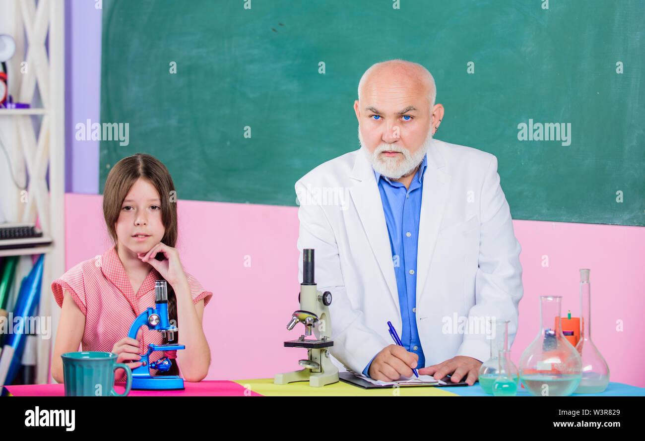 Formula. piccola ragazza con uomo tutor studio chimica. scienza classe. Utilizzare la lente di ingrandimento. Microscopia. Attrezzature di laboratorio. maturo docente di biologia. Allievo ragazza nel laboratorio scolastico. Immagini Stock