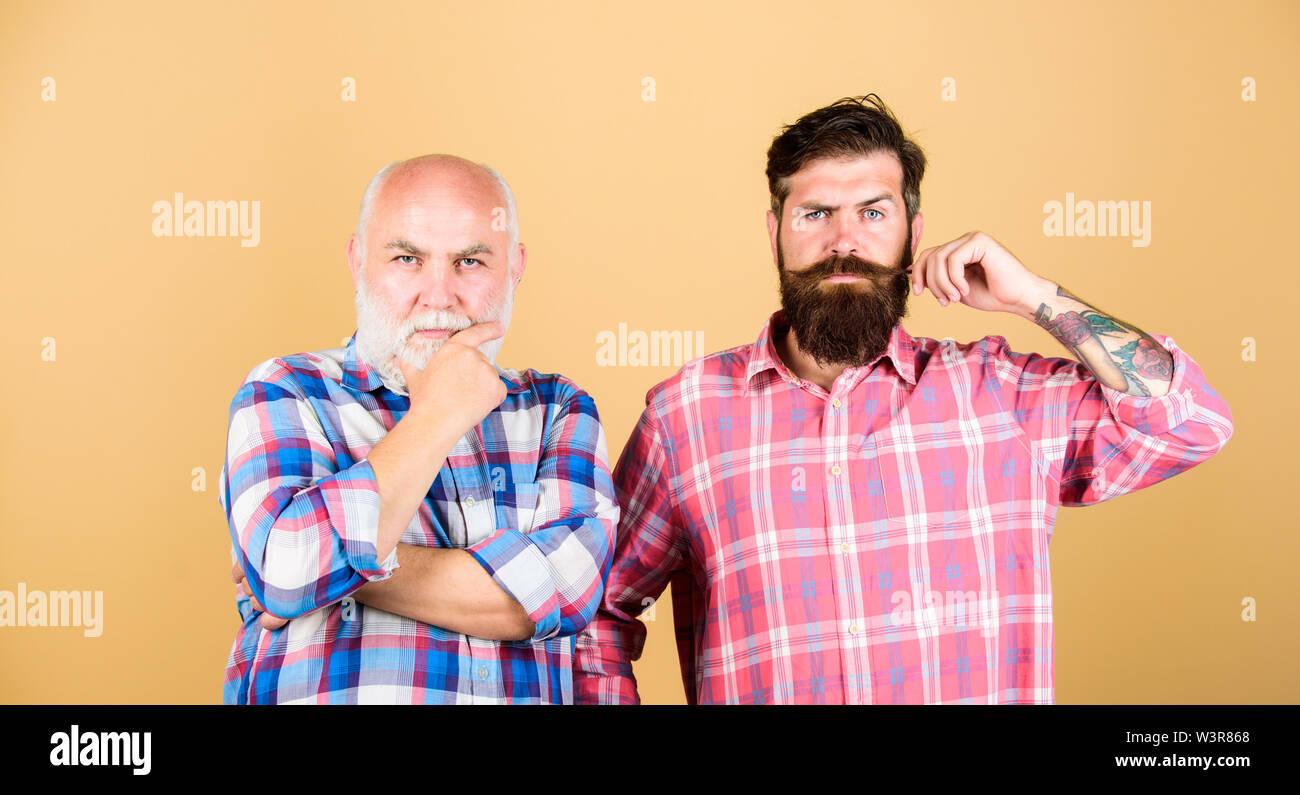 Barbiere maschio cura. scacchiera. padre e figlio famiglia. conflitto generazionale. due uomo barbuto senior e matura. barbiere e parrucchiere. gioventù vs vecchiaia confronta. il pensionamento. Foto Stock