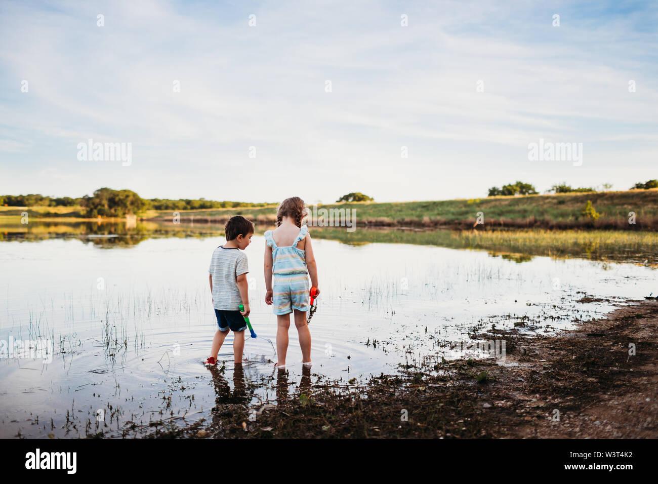 Ragazzo e ragazza cerca di pescare con reti a lago Foto Stock