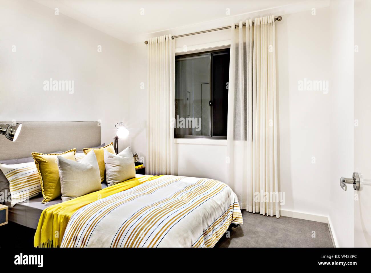 Camera Classic di una casa moderna con lampade da tavolo su avanti per i cuscini e il letto con piumino, vi è una finestra di vetro nera coperta con una tenda Immagini Stock