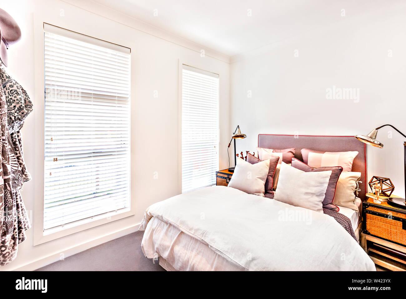 Camera moderna con cuscini sul letto con lenzuola e coperte accanto al caso di rattan e lampada da tavolo, la finestra viene chiusa e la luce del sole è venuto attraverso Immagini Stock