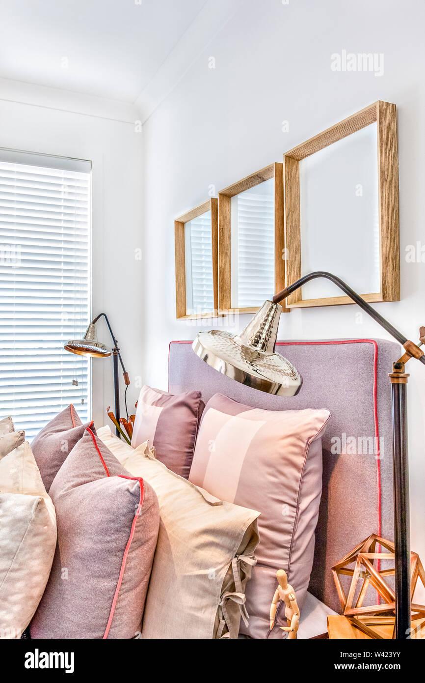 Camera da letto lussuosa con legno di elementi di fantasia e i cuscini vicino a partire dal lato con colore argento lampade da tavolo accanto a una finestra chiusa Immagini Stock