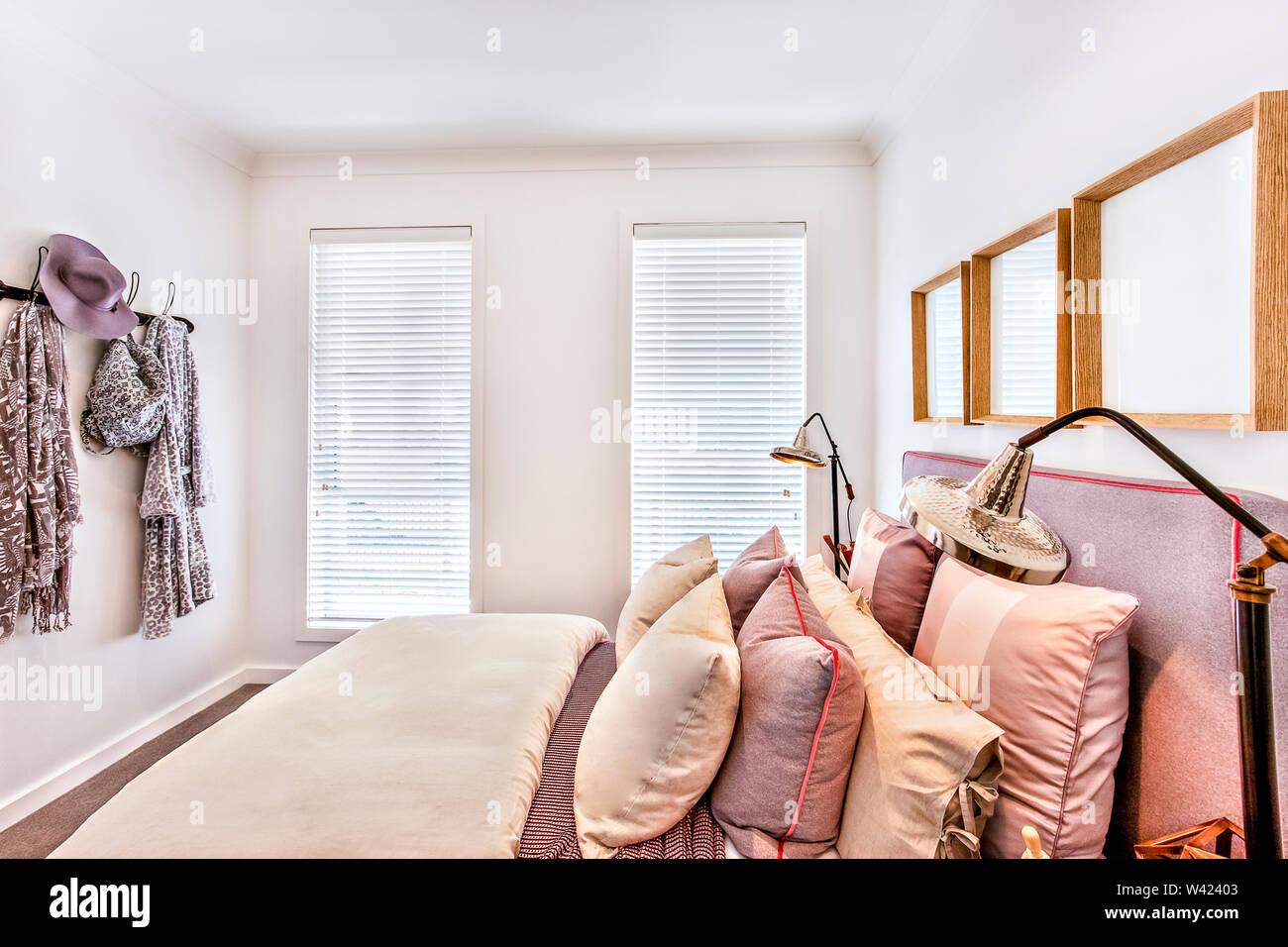La camera da letto di lusso closeup con lampada da tavolo e cuscini sul letto con una spessa coperta dalla vista laterale, windows coperto con filtro e chiuso, clo Immagini Stock