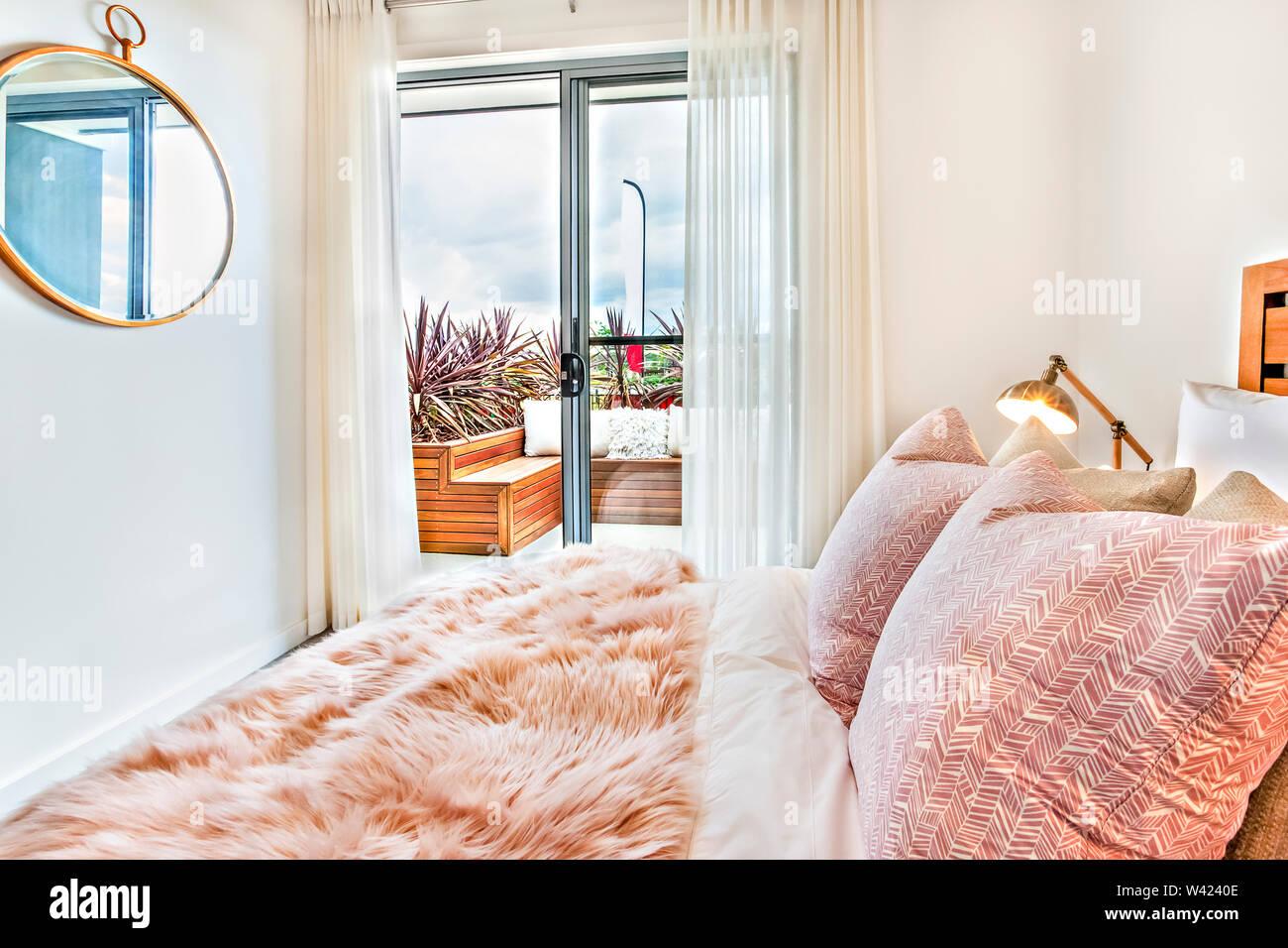 Camera da letto moderna close up illuminato dalla luce solare attraverso la porta della camera da letto compresa una pelliccia foglio letto vicino al specchio rotondo Immagini Stock
