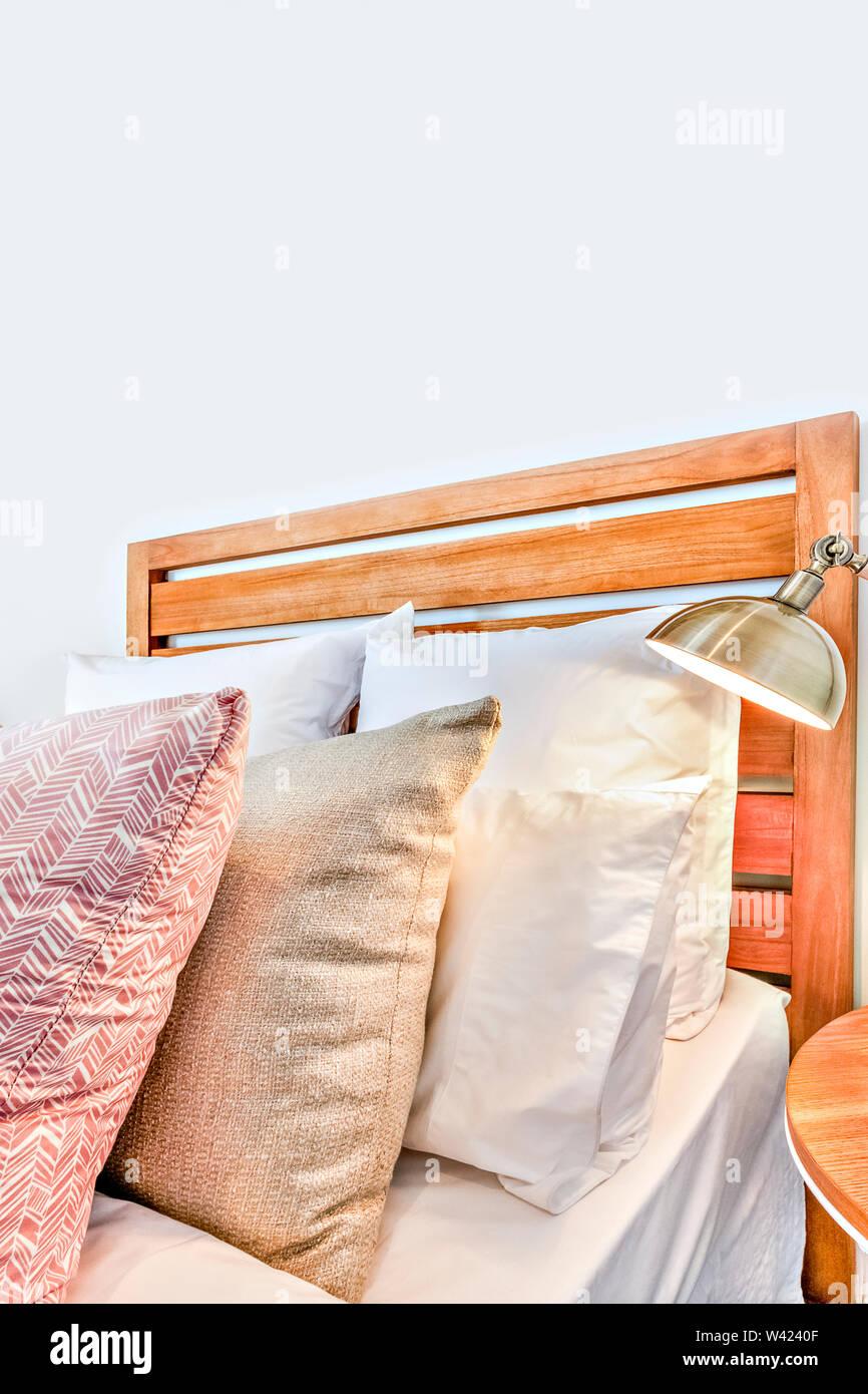 Lussuoso letto in legno con cuscini close up accanto a una lampada che illumina la stanza moderna Immagini Stock