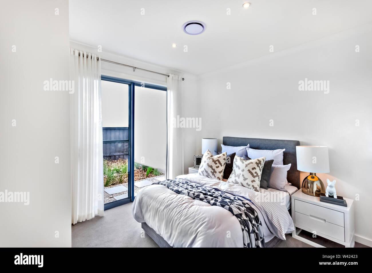 La camera da letto di lusso con decorazione bianco tra i quali coperte e cuscini vicino a lampade e pareti Immagini Stock