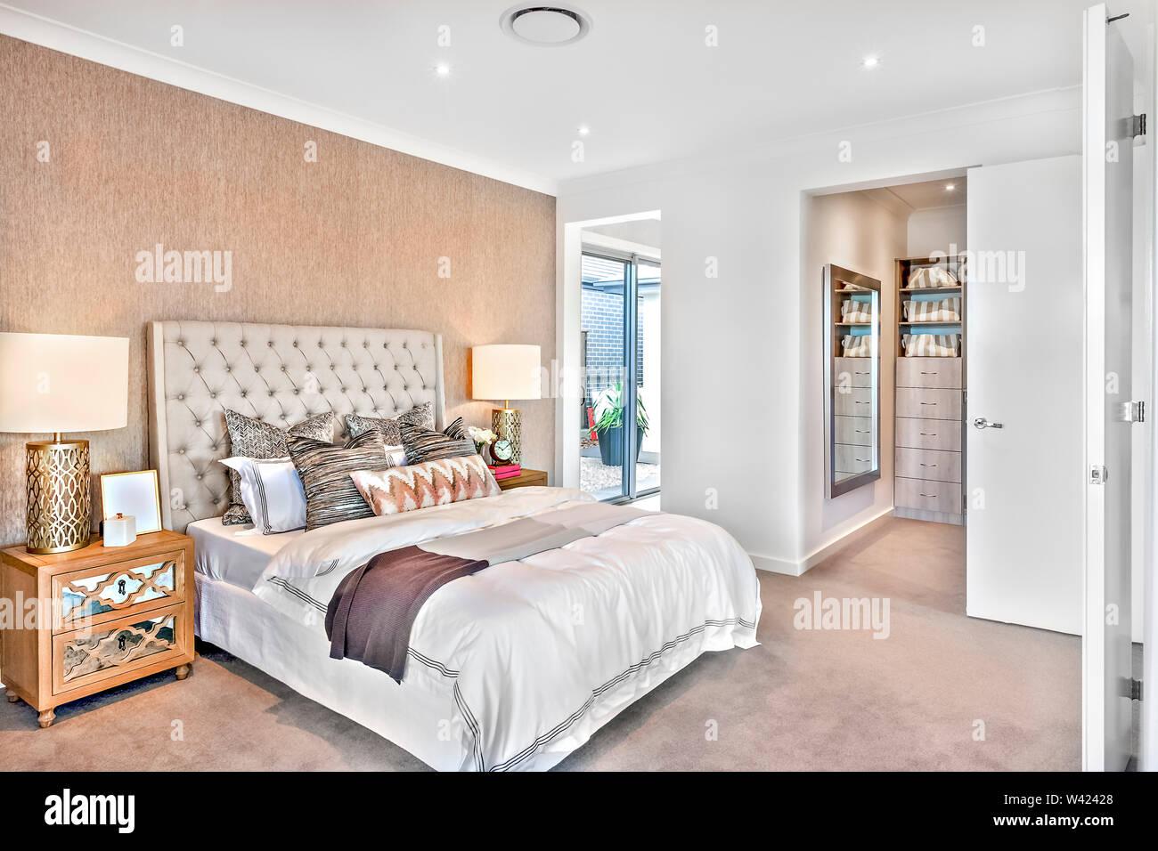 Camera da letto moderna decorazione con porte per esterno e lavanderia, vi sono luci lampeggianti sulla armadi accanto a cuscini e coperte sul letto Immagini Stock