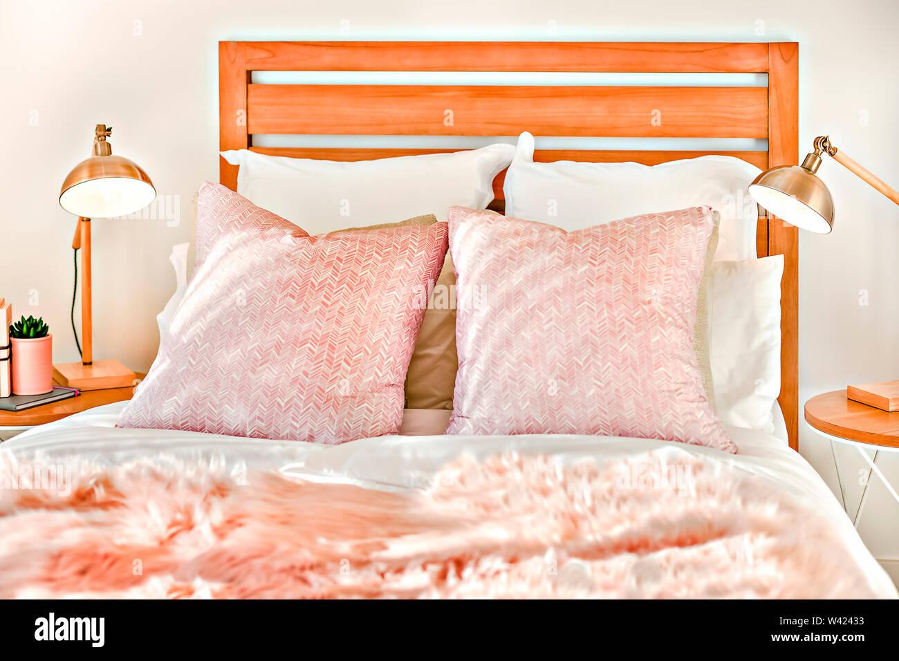 Letto matrimoniale con cuscini accanto a luci lampeggianti sulla tavola con decorazioni di fantasia in una casa di lusso Immagini Stock