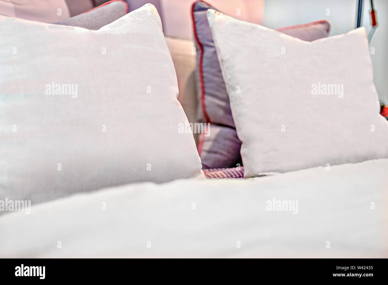 Cuscini con lettera design sul letto vicino fino in una casa di lusso o hotel Immagini Stock