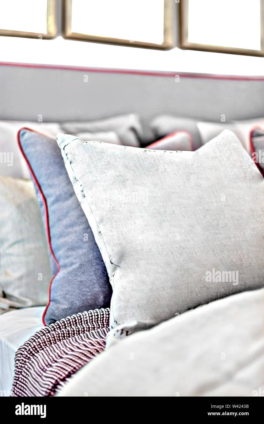 Cuscini sul letto closeup con lo sfondo sfocato in una casa moderna Immagini Stock