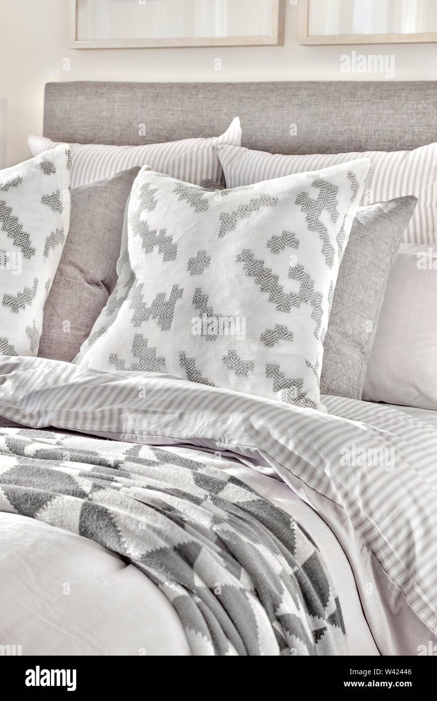Letto Moderno e cuscini con coperte con disegni astratti vicino fino in una casa di lusso Immagini Stock