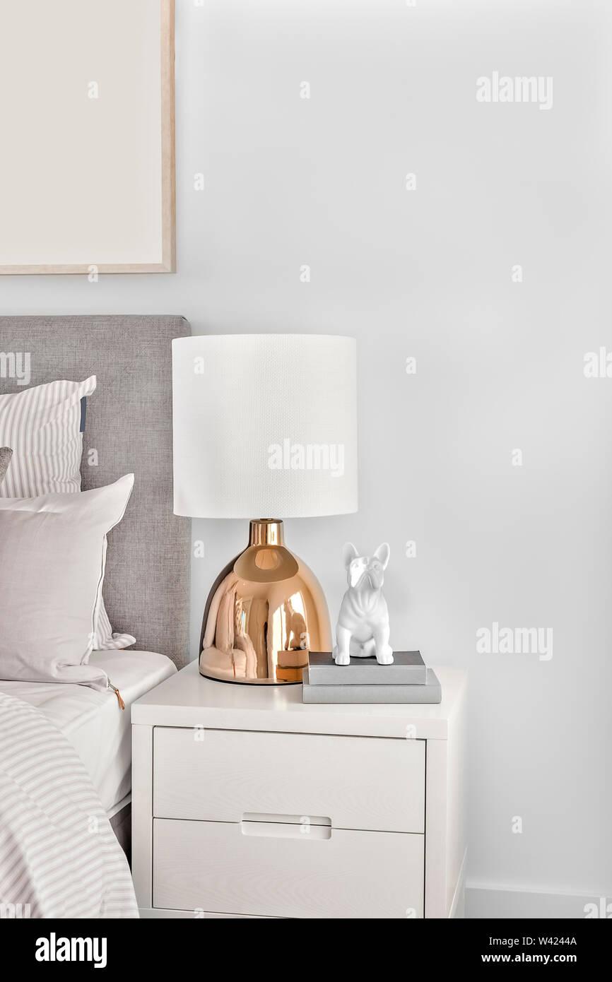 Camera moderna con un colore oro lampada da tavolo in metallo o legno armadio con libri e statua del cane accanto al letto con cuscini Immagini Stock
