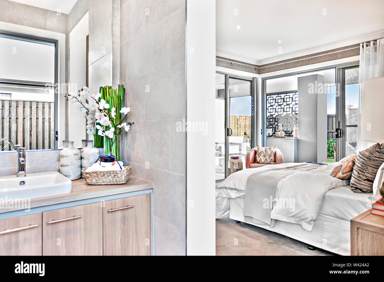 Bagno moderno attaccata alla camera da letto di lusso in una casa con un letto matrimoniale e di fogli accanto a porta aperta e windows all'esterno. Immagini Stock