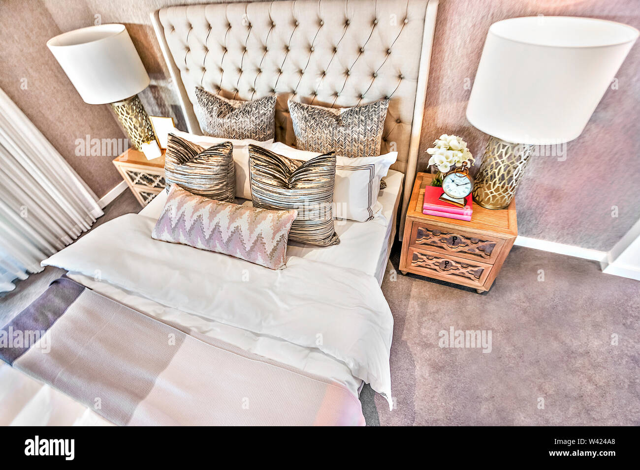 Vista superiore della camera da letto di lusso closeup con cuscini, fogli e spie del mobiletto in legno, colorata area perfetto anche fulmini, camera molto pulita. Immagini Stock