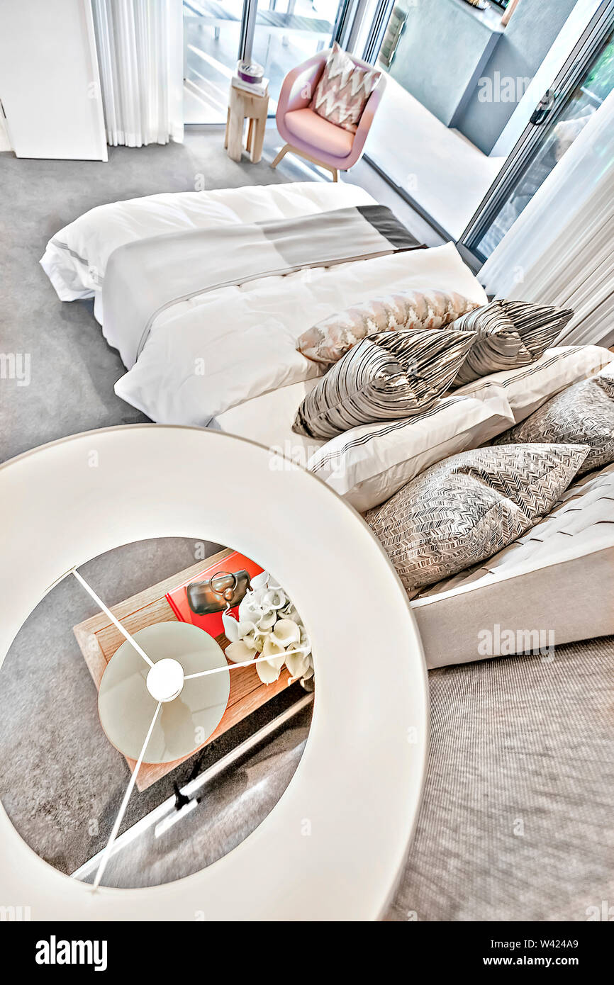 Camera da letto moderno angolo alto vista da sopra la lampada sul tavolino accanto al letto i cuscini e le lenzuola accanto alle porte di vetro colorato, luogo perfetto anche l Immagini Stock