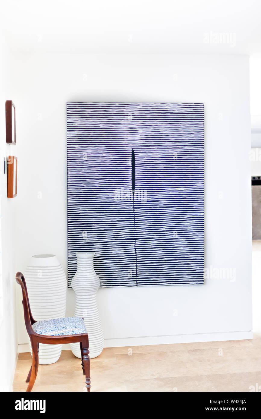Camera elegante con una sedia in legno e vasi e un pattern opere d'arte appese alle pareti bianche in casa di lusso Immagini Stock