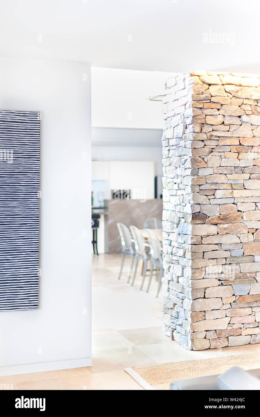 Corridoio moderno entrata di una casa o un hotel attraverso il muro di pietra e muro bianco che illumina con la luce solare Immagini Stock