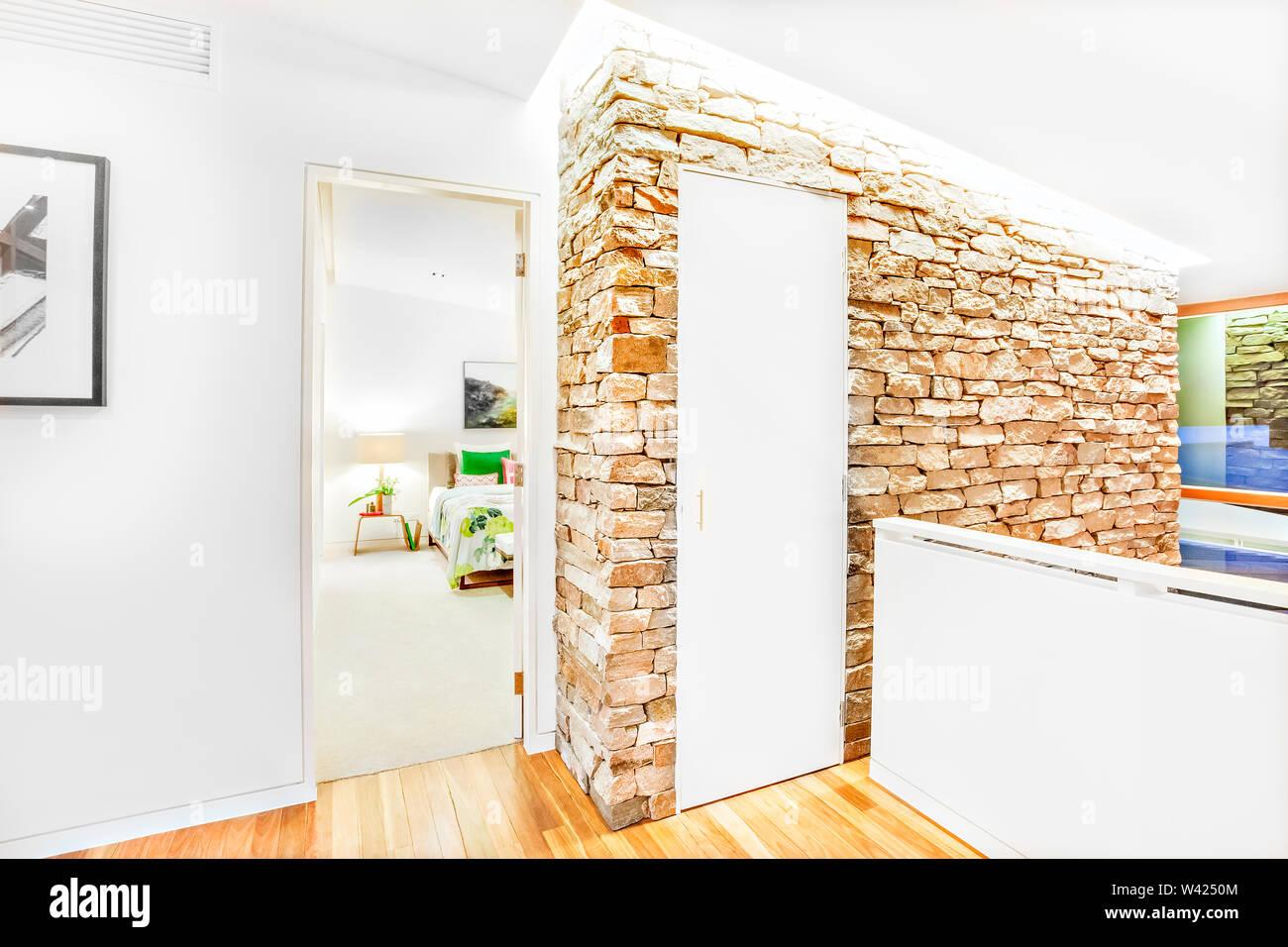 Muro di pietra, la porta chiusa e una posizione aperta entrata alla camera da letto attraverso il pavimento in legno in corridoio, le pareti bianche sono attaccati alle pareti di mattoni e illuminat Immagini Stock