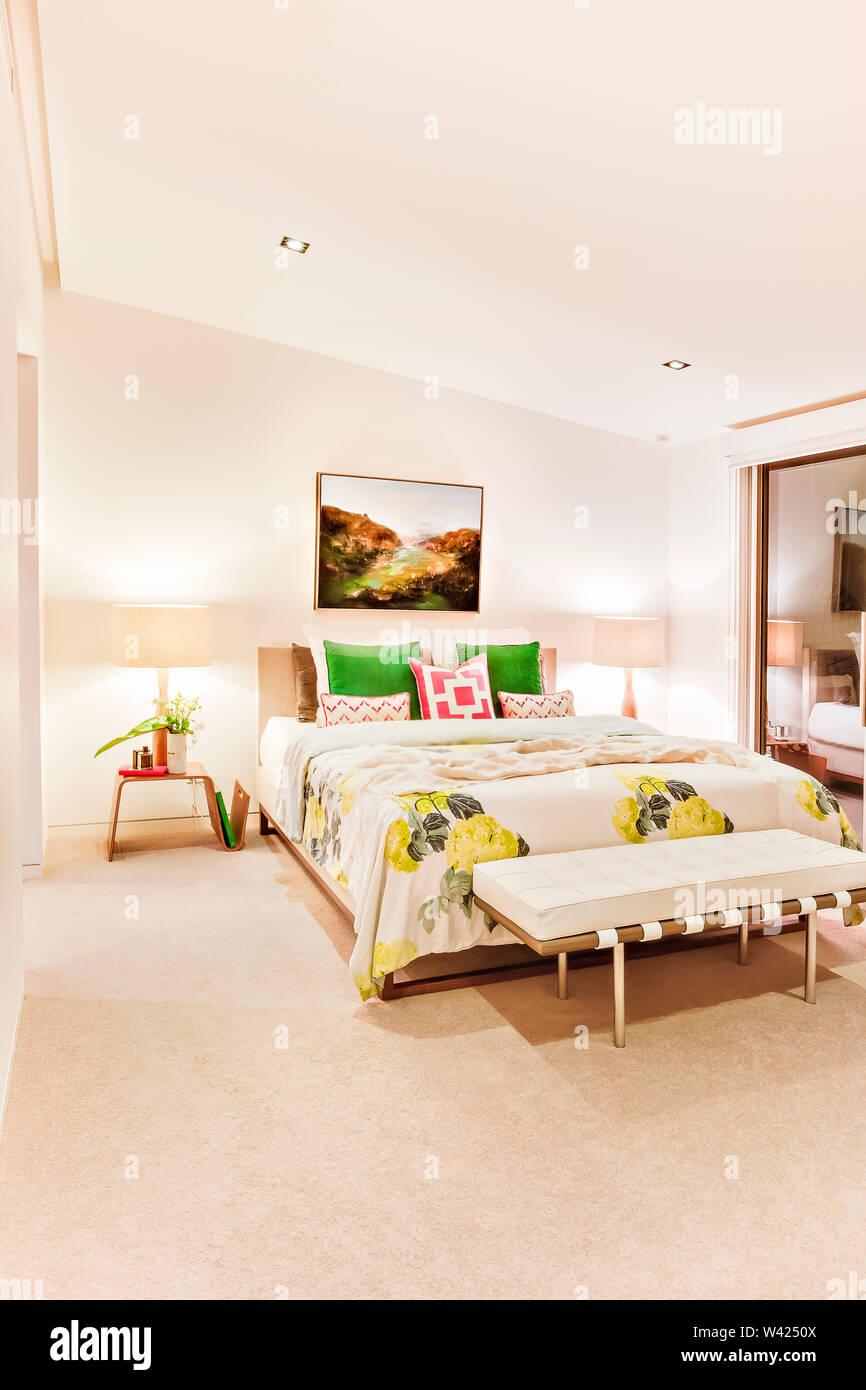 Moderno bed room interno con pareti bianche brighened con luci compresi i cuscini sul letto foglio e un piccolo tavolo con lampade accanto al vetro windo Immagini Stock