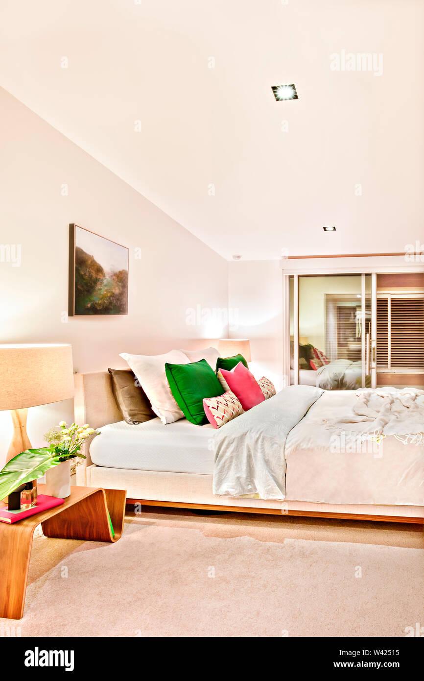 La camera da letto di lusso illuminato di notte con la porta d'ingresso verso l'interno che ha un tavolo di legno lampade e coperte di fiori sul letto con cuscini Immagini Stock